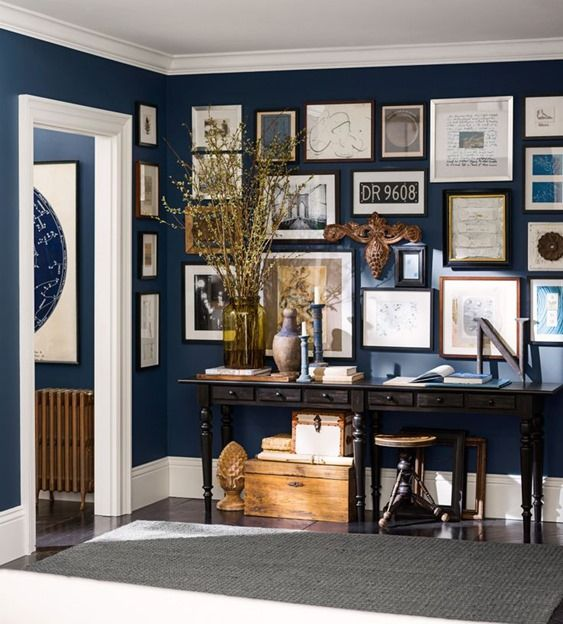 Pottery Barn's partnership with Sherwin Williams Naval blue as the backdrop to this well curated wall gallery, it's navy blue perfect