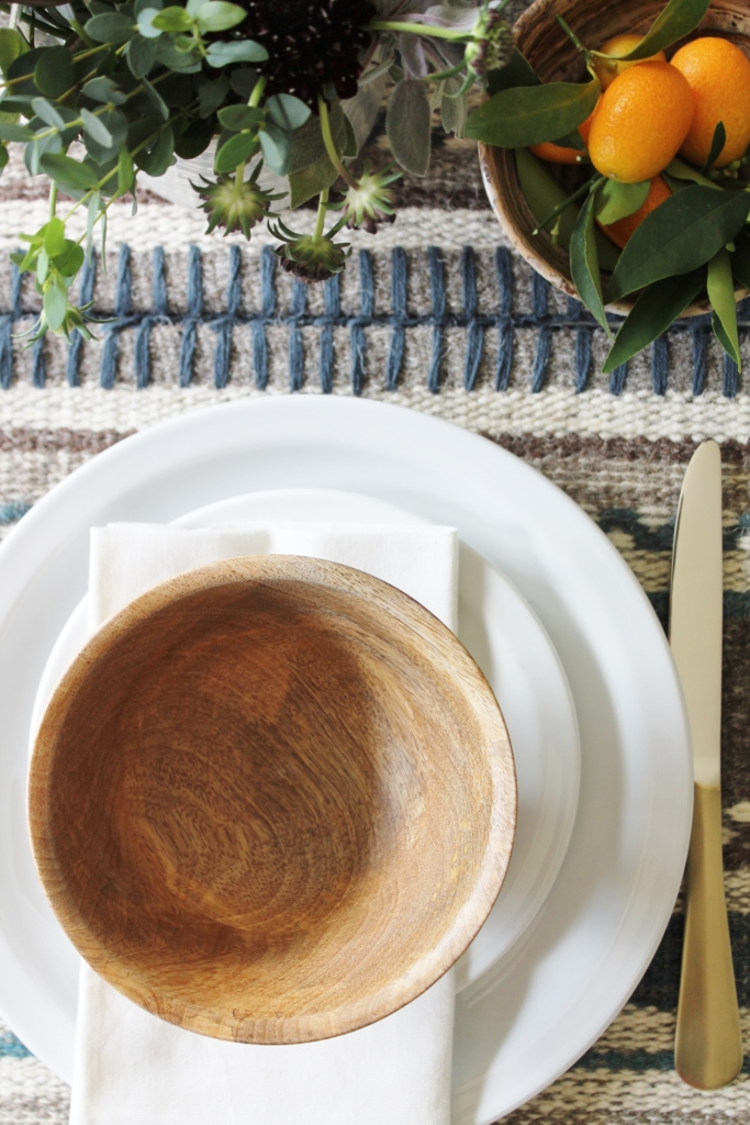 rustic table setting from all modern wood bowls, gold flatwear & kilim tablerunner
