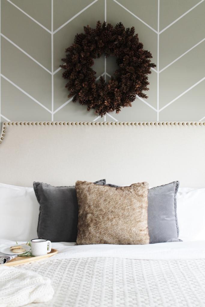 simple modern farmhouse holiday bedroom. Christmas decorating. Pine cone wreath, fresh greenery, plaid & cozy details